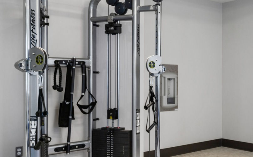 bright fitness room with weight and cardio equipment